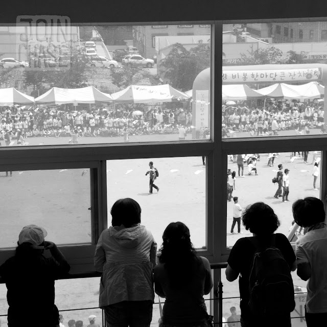 Parents watching Sports Day through a window at Bibong Elementary in Ochang, South Korea.