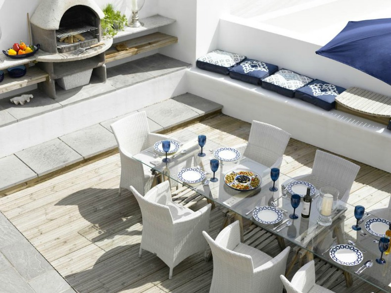 Coastal outdoor dining room with fireplace