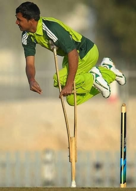 Pakistani man just after throwing, balancing on end of a crutch, playing cricket