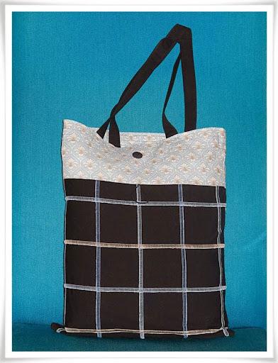 Kasse i svart tyg med rutor sydda med flatlock-söm