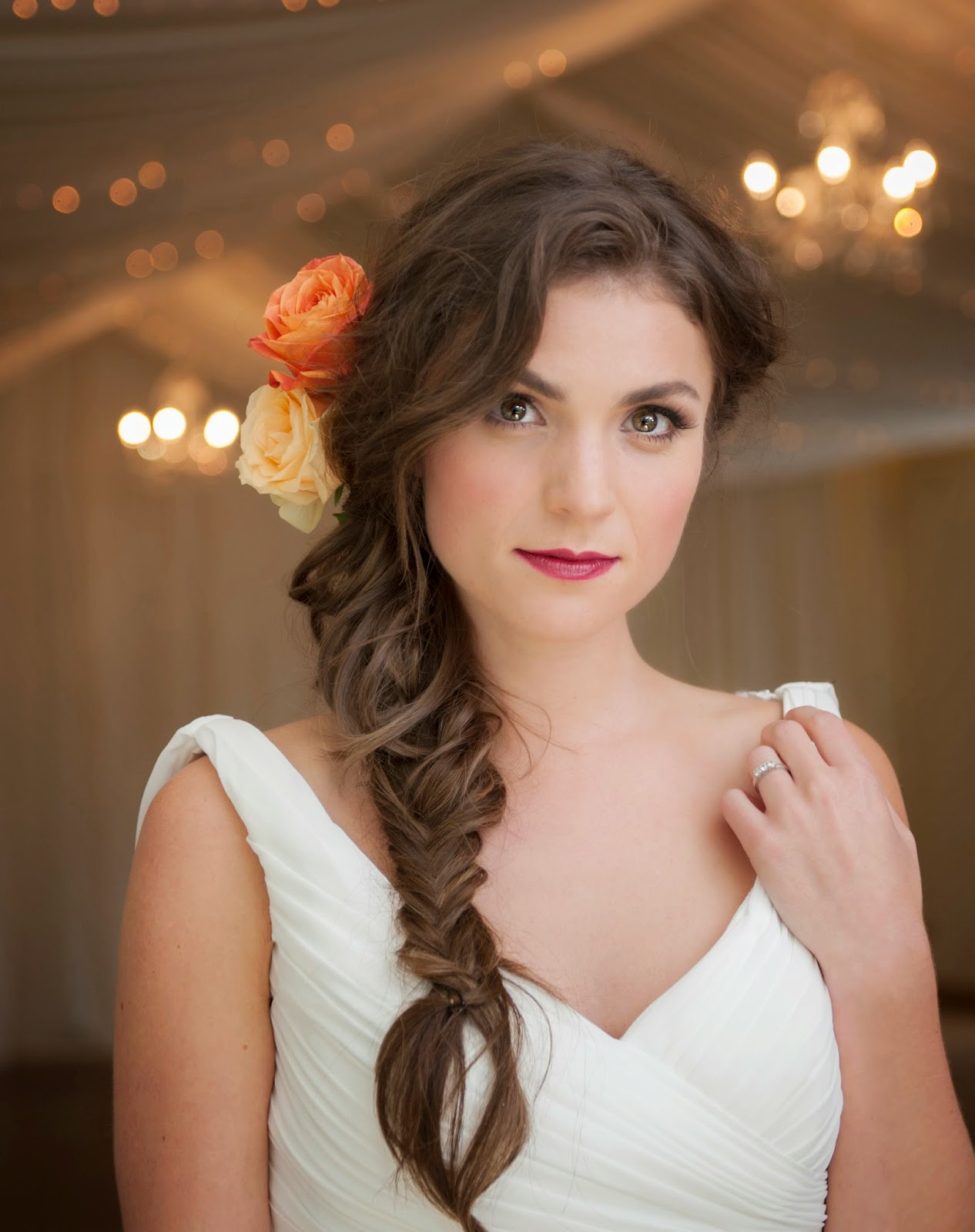 model wears her hair softly waved in a loose braid with flower accessories
