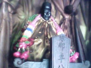 Patung hitam dengan imej lelaki memakai songkok
