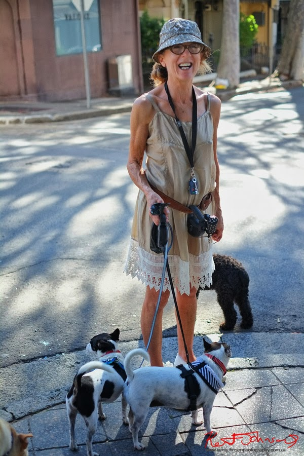 Woman walking two Jack Russell dogs in Paddington Sydney, champagne slip dress with lace hem, cotton cammo bucket hat. Photo by Kent Johnson.