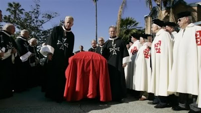The coffin of Carl Jr. founder Carl Karcher passes through an honor guard representing the Knights and Dames of Malta, left, in black, and the Knights and Ladies of the Holy Sepulchre, right, in white at the funeral services for Karcher at St. Boniface Catholic Church in Anaheim, Calif