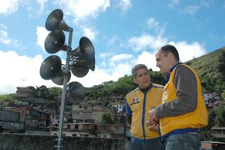Agente de Defesa Civil Eduardo Flores e o Subsecretário de Meio Ambiente e Defesa Civil André de Mello conferem o acionamento simulado do conjunto de sirenes instalado no Rosário