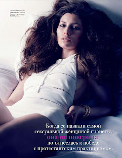 Jessica Biel in a bodysuit laying on a bed