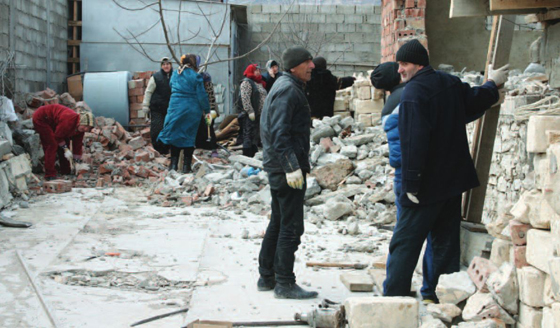 Local residents cleaning up the debris of a house destroyed in a counterinsurgency operation in Novyi Agachaul,  Dagestan. (Photo by Varvara Pakhomenko