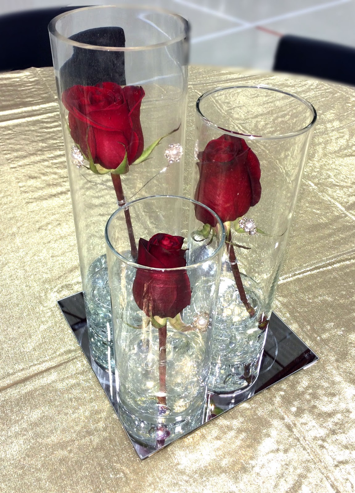 The Centerpieces Were 3 Vases Of Varied Height With A Burgundy Rose In Each Vase And Some Pearl Diamond Bling Wired To Roses These Sitting Atop