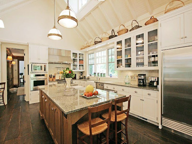 kitchen with a frame high ceiling and a skylight, rustic wood floors, white cabinets with glass upper cabinetry and an island with granite counters