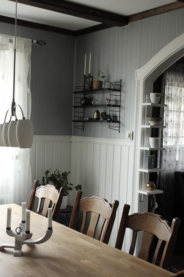 stringhylla i vardagsrummet, matsal med matbord och sex stolar, vardagsrum i grått och vitt, smal vit hylla från em möbler, guld i inredningen, vit taklampa, vit bröstpanel
