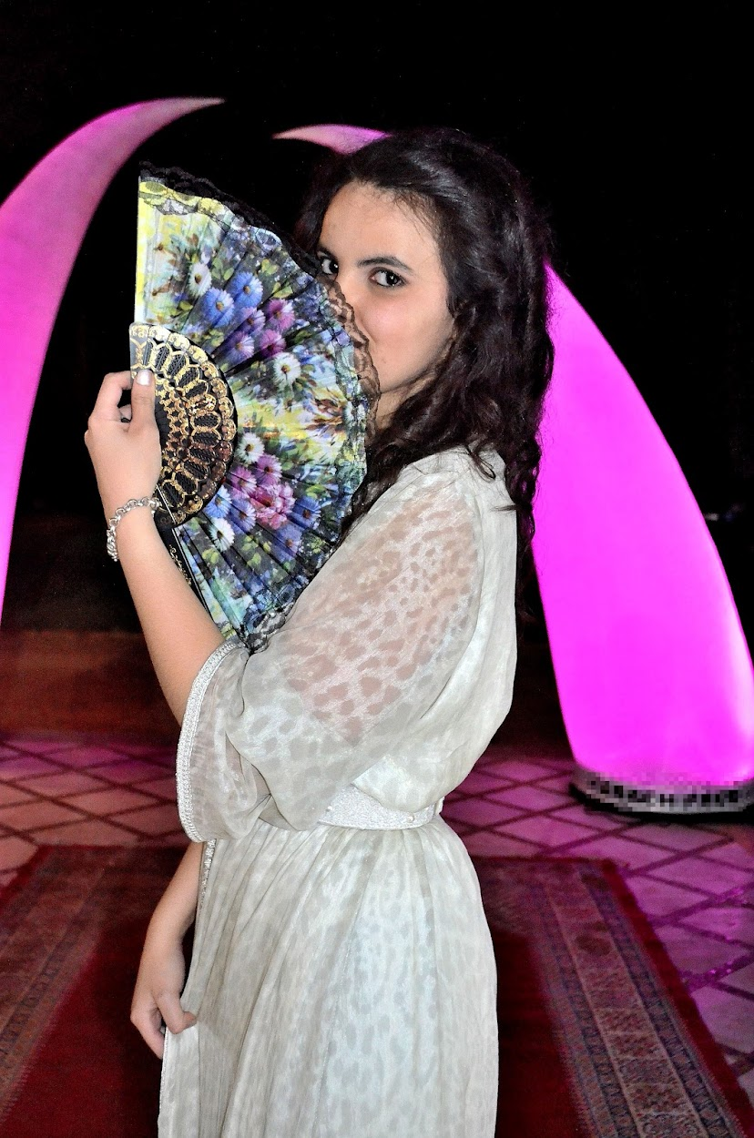 the serial shopper holding a fan during a moroccan wedding
