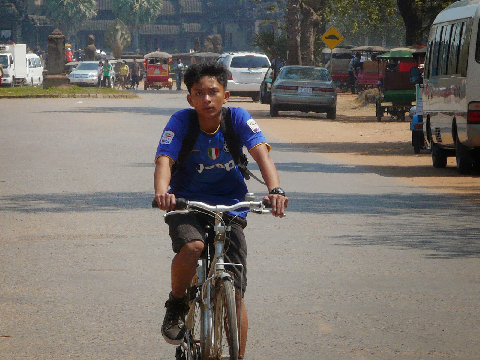 khmer boy riding bicycle near Angkor Wat