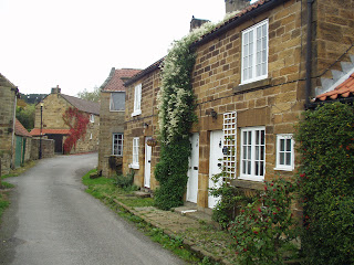 A colour photo of a narrow winding lane lined with stone houses, they are small with creepers running up the wall, quite pretty