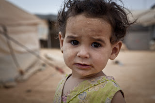 Nawara, five, peers out from her tent in Za'atari Refugee Camp, Jordan