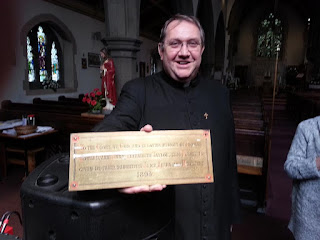 Father David in clerical dress holding out a brass plaque.