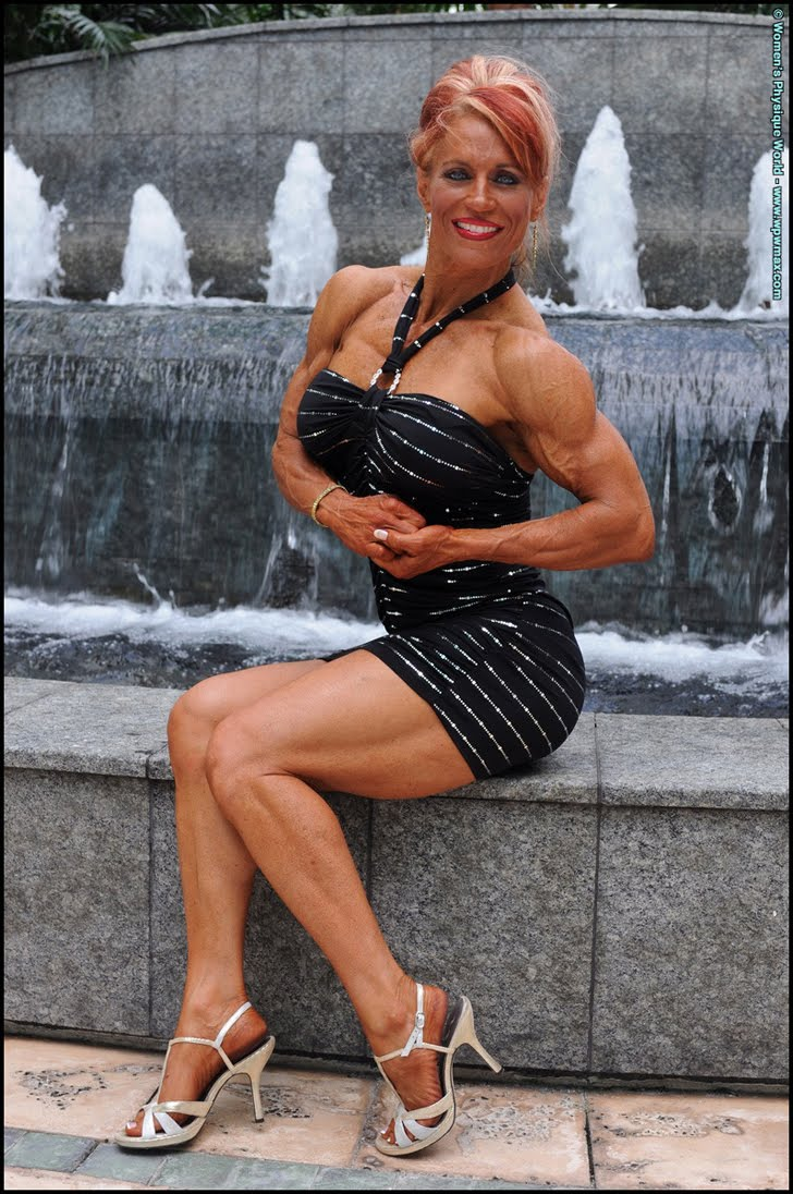 Theresa Hendricks Posing Her Fit Muscles In A Black Dress