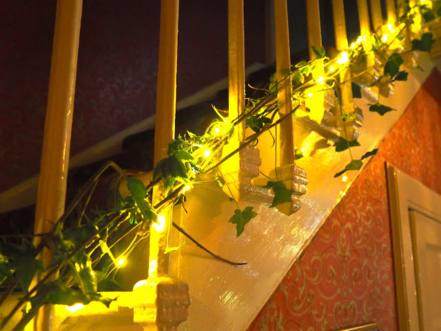 Stair case in the hallway decorated for Christmas with twinkly lights and green leaf foliage