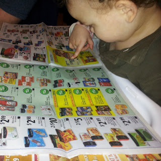 2 year old reads the grocery store flyer like it's a book
