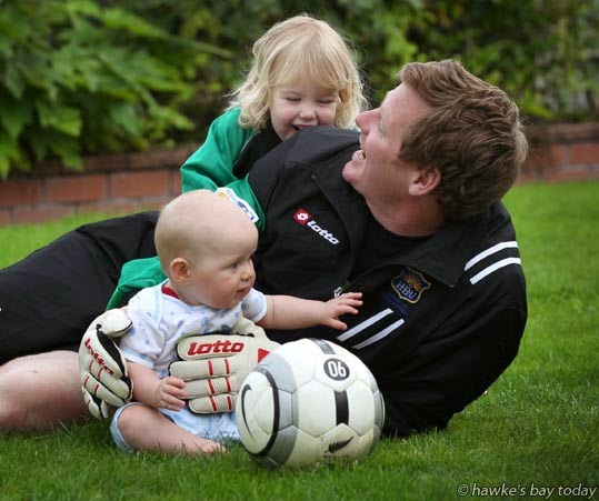 Richard Gillespie, Napier, goalie, Hawke's Bay United soccer team, used to play for Waitakere (who he'll be playing on Sunday), with his children L-R: Cooper, 6 months, Kayla, 2 (wearing his old Waitakere strip) photograph