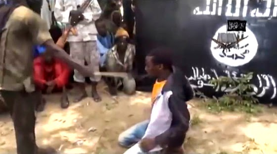 A video posted by Boko Haram shows a member whipping a Nigerian citizen. (Screen capture from YouTube video)