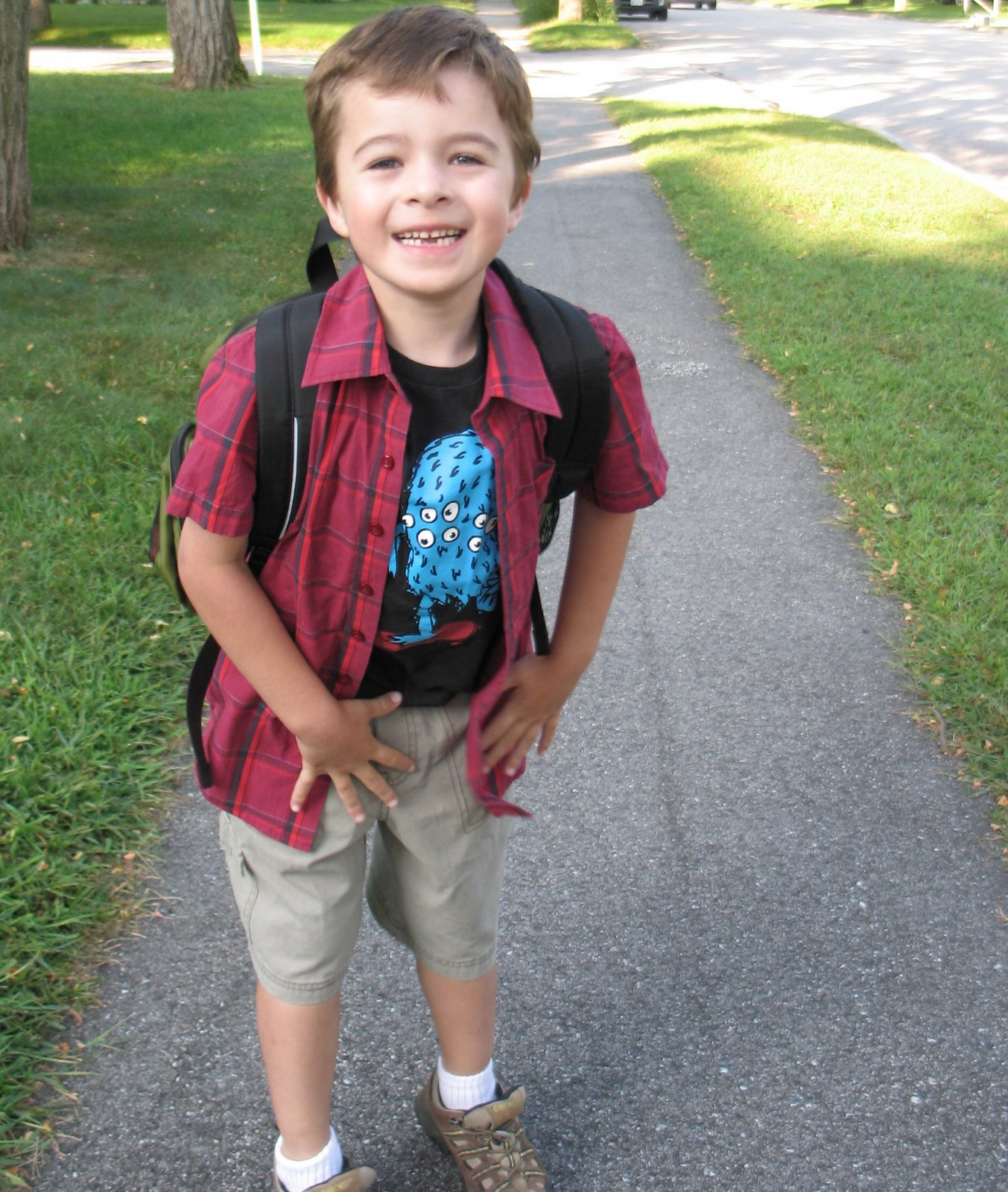 Boy with backpack on, plaid shirt, monster tshirt and shorts. He has a big smile.
