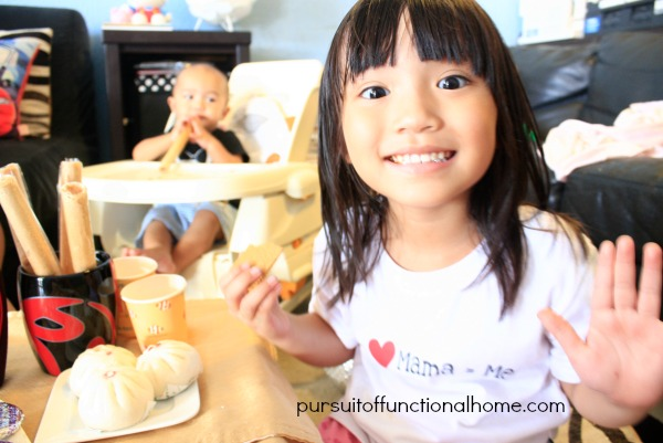 Indoor Family Picnic by pursuitoffunctionalhome.com. Little girl smiling and behind her is her brother sitting on a high chair nibbling Barquillos.