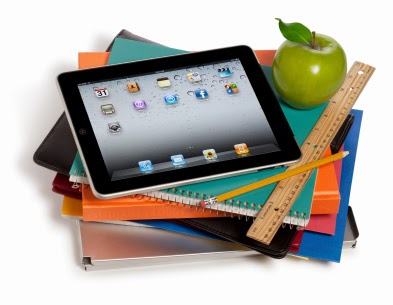 Image of an iPad sitting on a pile of books with and apple and a ruler