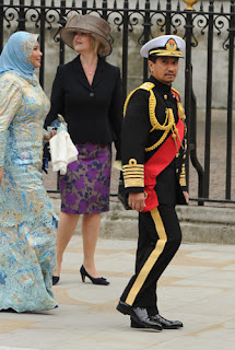 Hassanal Bolkiah, Sultan of Brunei (r.) arrives at the West Door of Westminster Abbey.