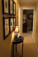 Decoracion de pasillo con cuadros y una mesita con luz en una de las paredes del pasillo