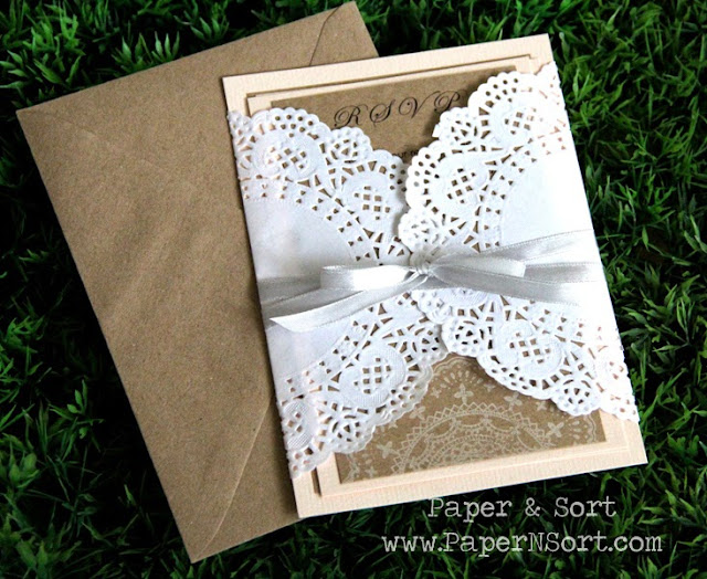 romantic wedding invitation in light peach made of kraft paper, paper lace doily and wrapped aroung in light grey ribbon