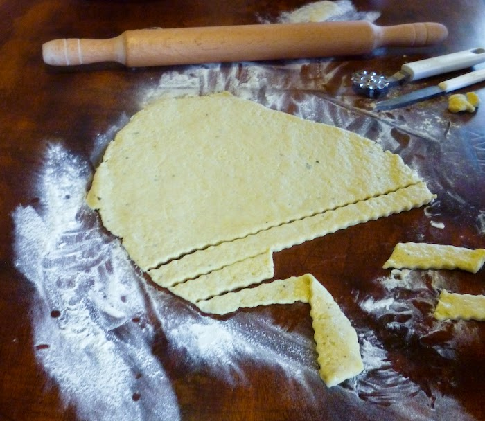 Rolling pin, rolled dough and wheel cutter on the table
