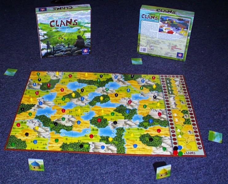 the board for Clans: a series of terrain types (yellow steppes, green forests, light green grasslands, and grey mountains, along with blue lakes). and the scoring track/epoch track on the right side of the board. Each terrain has one small wooden hut in one of five colours: red, green, yellow, black, and blue. There is a small wooden disk for each of these five colours sitting at the beginning of the scoring track, and each of the five spaces on the epoch track has a yellow wooden token. Around the board are the coloured hut tiles, with the green and yellow ones face up and the others face down. Behind the board is the box, showing the attractive and colourful design on the cover.
