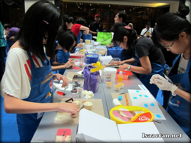 The contestants deep in concentration to make and decorate their cupcakes