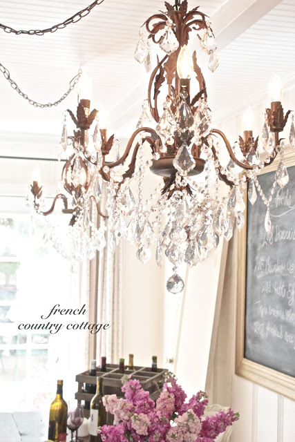 Two chandeliers above a farmhouse dining table with french doors in the back