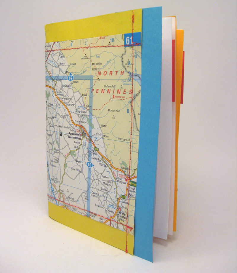 notebook made from old map pages and a sewing machine
