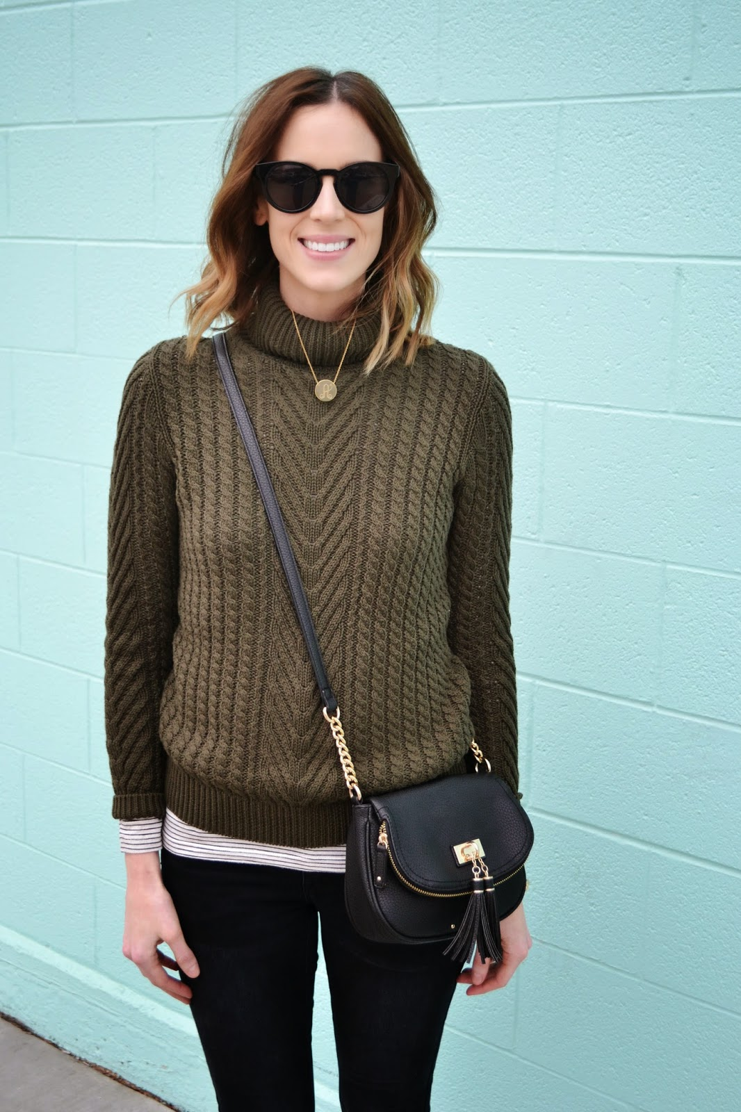 olive green turtleneck, black and white striped tee, black jeans, black booties, black and gold