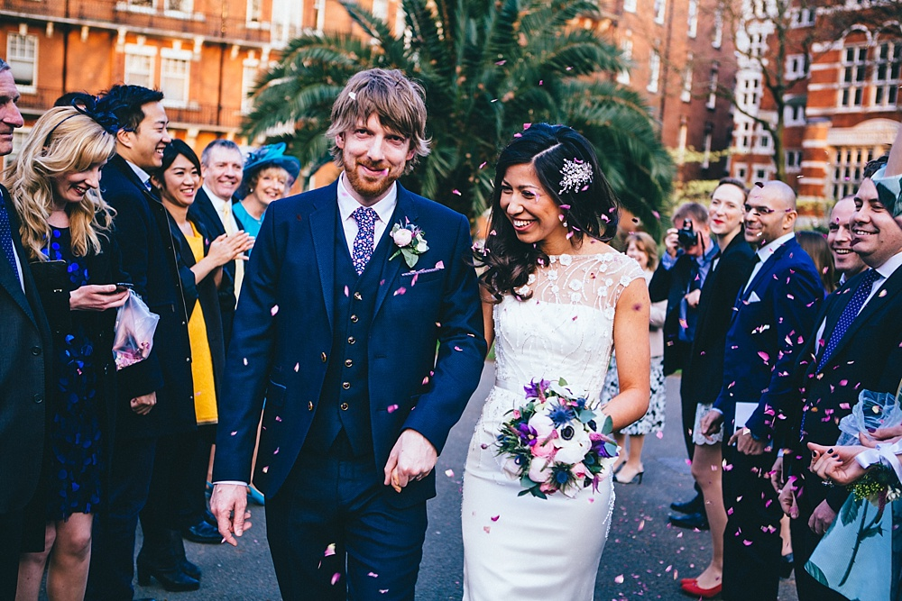 couple are showered with confetti after their wedding ceremony smiling and happy wedding photograph