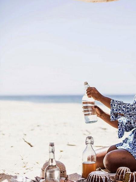 Szklane butelki z wodą na pikniku na plaży