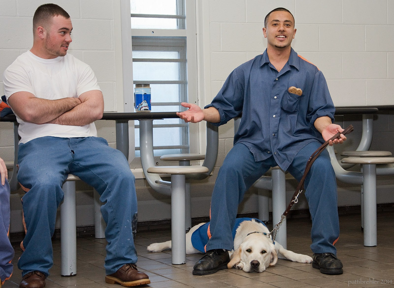 Two young men dressed in prison blues sit on cafeteria stools. The man on the right is gesturing to the camera, his yellow lab is  lying between his legs facing the camers. The man on the left has his arms folded and is looking at the other man.