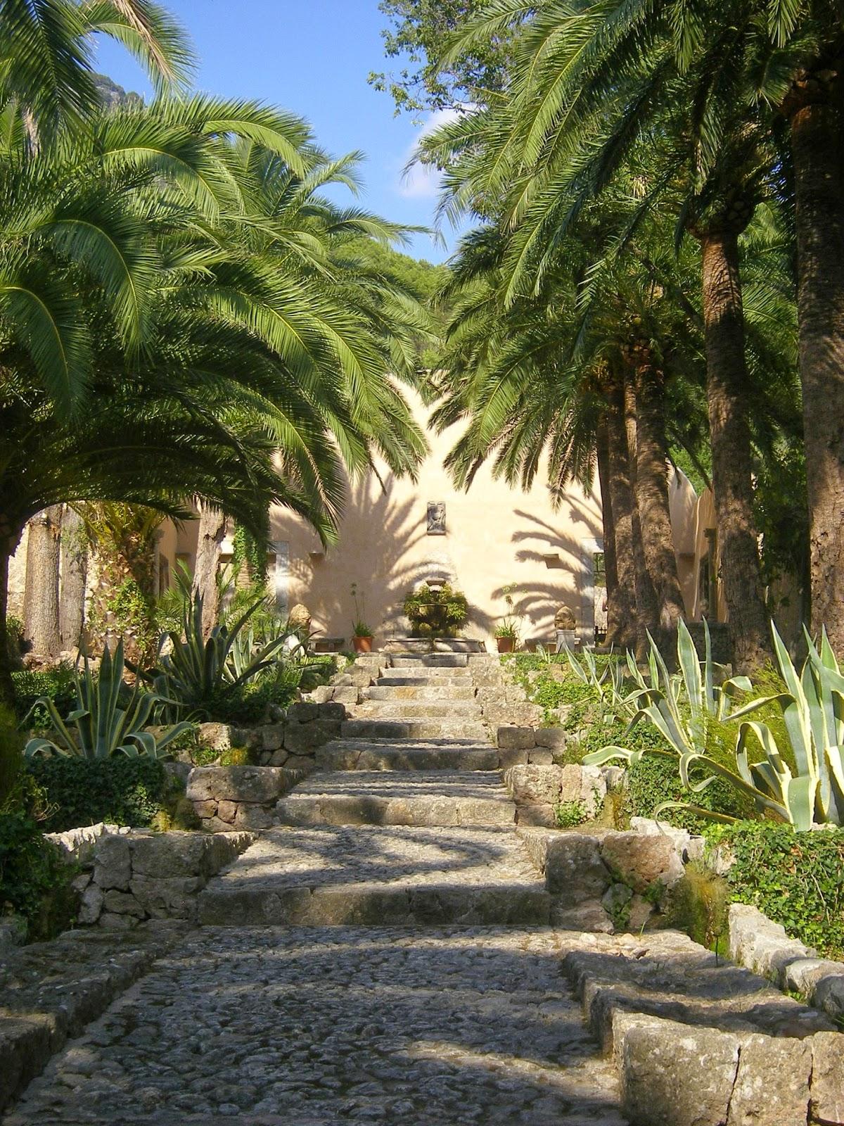 Lange nach oben führende Treppe die von Palmen und Blumen gesäumt wird