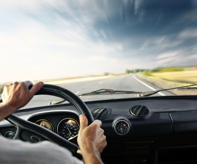 Se ven dos manos que agarran el volante de un coche y la carretera que se extiende hacia el horizonte