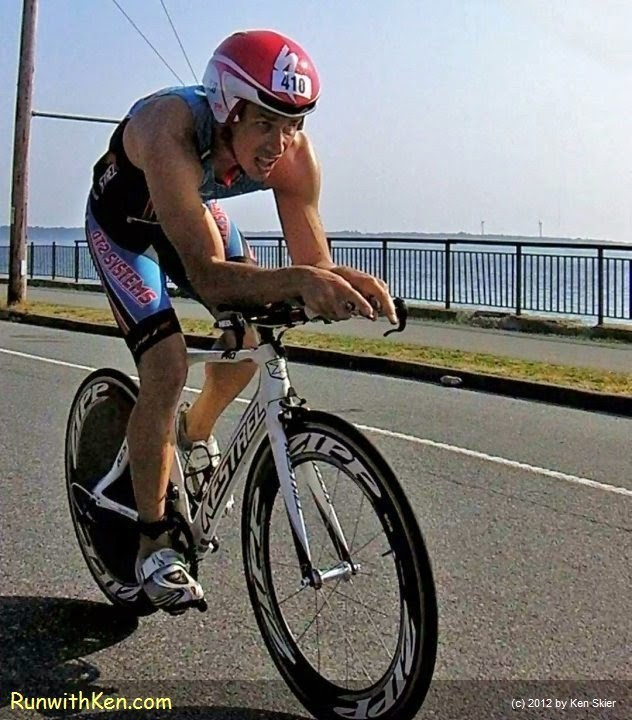 Up-close action photo of a cyclist, bicycling at the Whaling City Triathlon in New Bedford, MA, July 1, 2014.  Photo by Ken Skier, the Bicycling Photographer.  (RunwithKen.com)  The Whaling City Triathlon is produced by Sun MultiSport Events.  (sunmultisportevents.com)