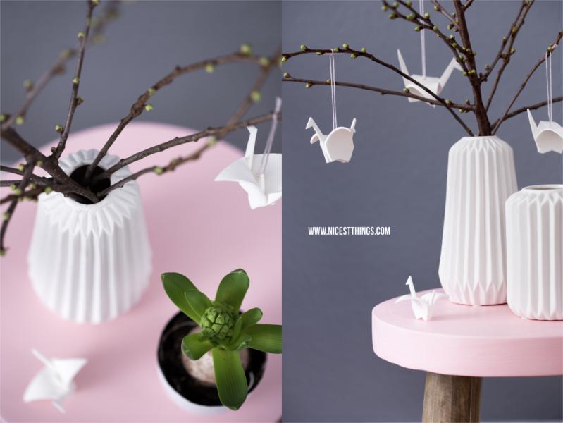weisse porzellanvase auf rosa hocker