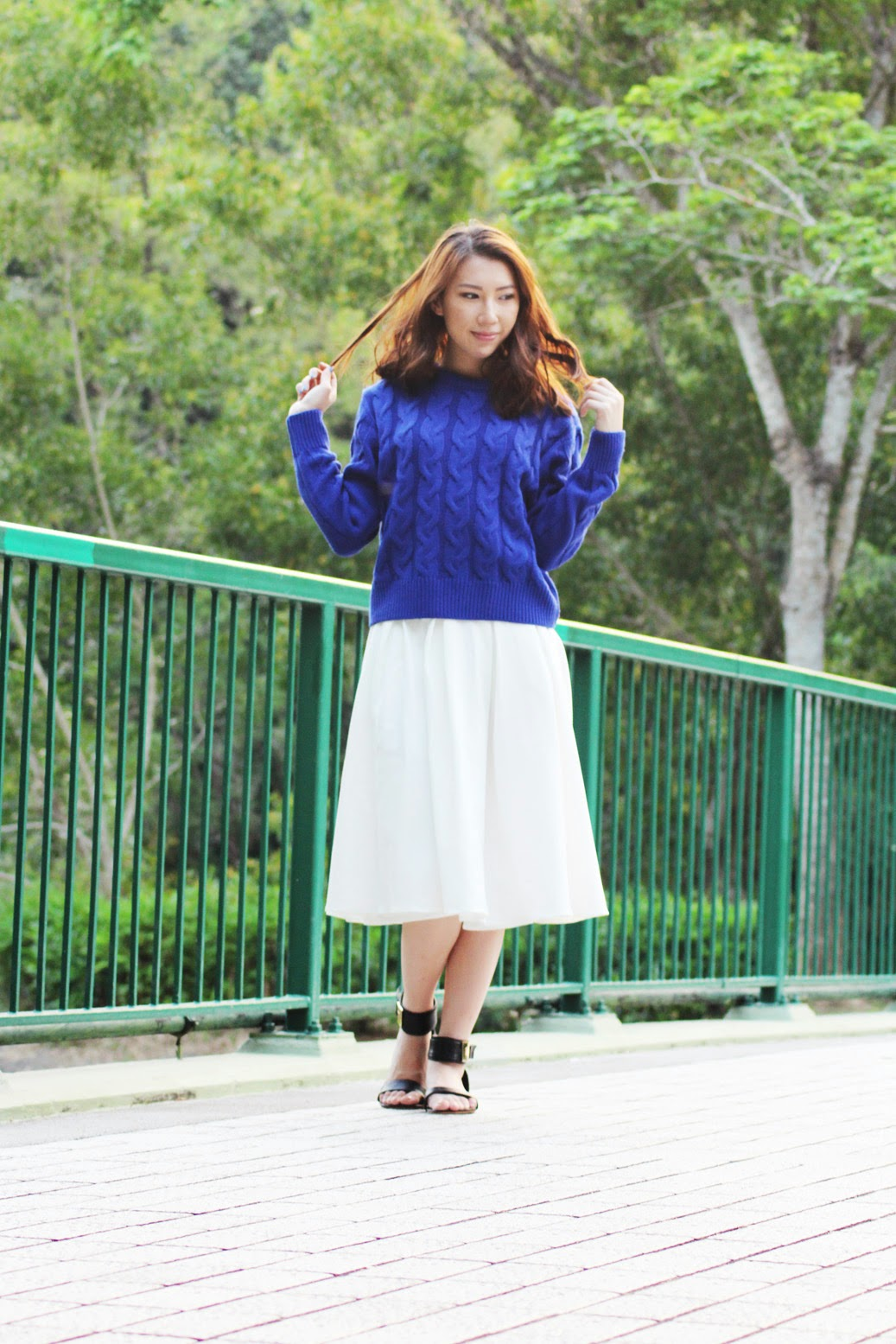 Styling blue sweater with flared white midi skirt and gold buckled sandals
