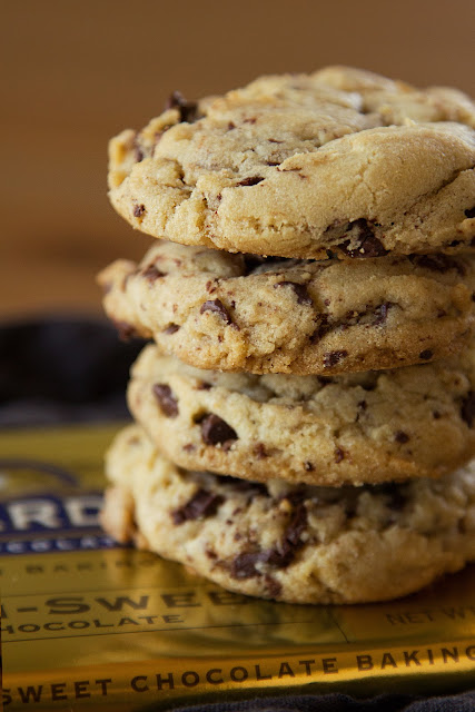 A stack of freckled chocolate chip cookies sitting on top of a Ghirardelli chocolate bar