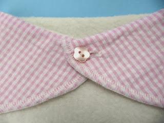 Pink bandana bib fastened with pink flower button