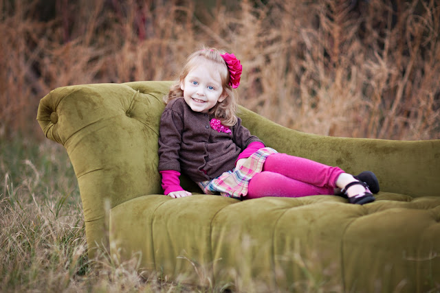 Child poses on chaise wearing a perfectly put together outfit