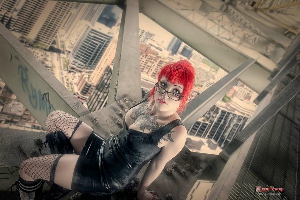 photo de charles bodi representant une femme tatouée aux cheveux rouges en robe de cuir noir asise sur une structure métallique
