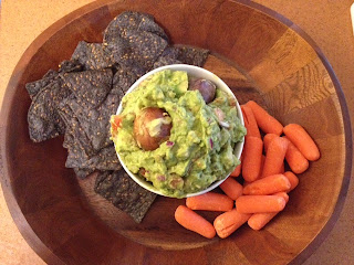Guacamole served with blue corn chips and baby carrots