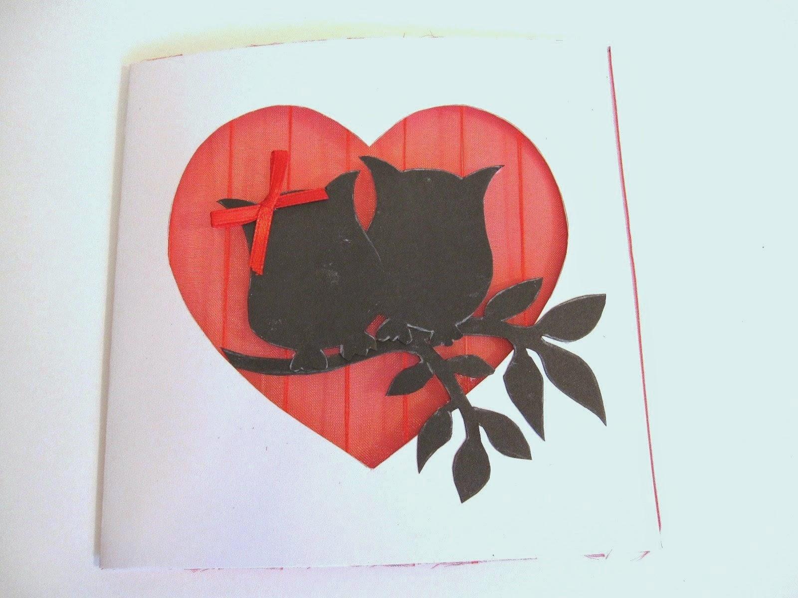 tarjeta blanca de felicitación con corazón calado con fondo de gasa roja y siluetas delante de dos búhos y rama de árbol